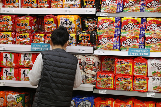 A customer shops at the ramyeon section of a supermarket in central Seoul. [YONHAP]