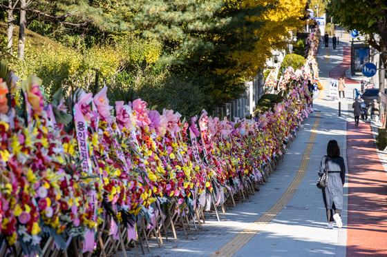 Flower wreathes sent by the people who support Prosecutor General Yoon Seok-youl stand along the pedestrian walkway in front of the Supreme Prosecutors' Office in Seocho District of southern Seoul on Oct. 29. Conservative civic groups who sent the majority of flowers removed them on Monday as controversy about Yoon's political future grew.  [YONHAP] 〉