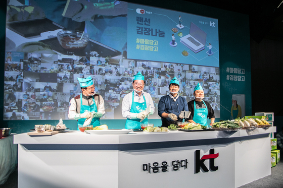 From left, Lee Chul-kyu, KT vice president in charge of network, and Ahn Sang-don, KT vice president in charge of the legal department, participate in the winter kimchi making event held at KT Square in central Seoul on Wednesday. The annual charity event was held online this year due to Covid-19. [YONHAP]