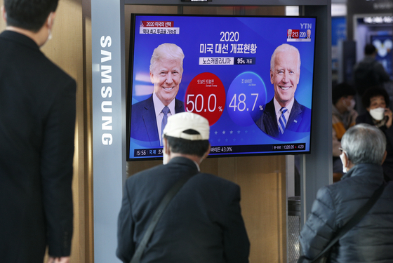 Koreans at Seoul Station on Wednesday afternoon watch through the TV monitor the tense U.S. presidential race between Republican President Donald Trump and Democratic candidate former Vice President Joe Biden unfold. [NEWS1]