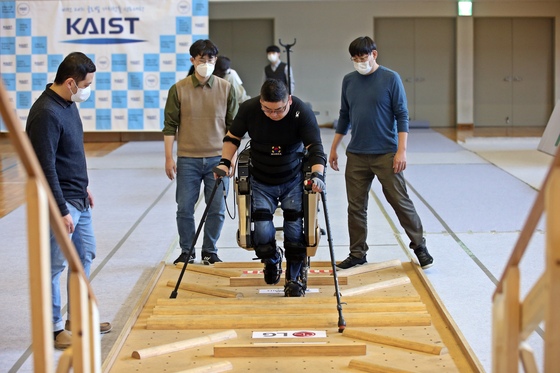 Kim Byeong-uk, who is paralyzed, walks over obstacles with an exoskeleton developed by a KAIST team and Yonsei University's Severance Hospital during a Cybathlon competition held in Daejeon on Wednesday. The international competition was supposed to take place in May in Switzerland, but it was postponed due to the Covid-19 pandemic. [YONHAP]