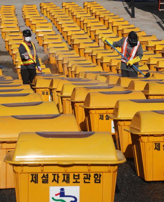 Workers in Suwon, Gyeonggi, on Thursday clean plastic containers in which calcium chloride is kept in preparation for the upcoming winter season. Calcium chloride is scattered over to melt snow. [NEWS1]