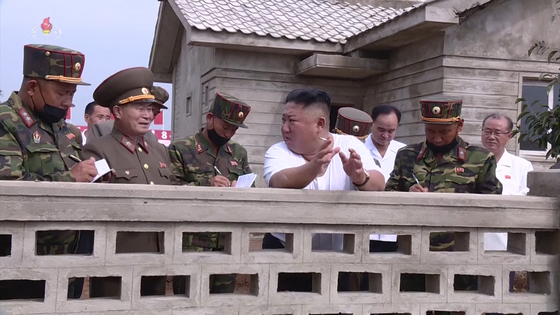 North Korean leader Kim Jong-un, center, wearing white, smokes a cigarette as he visits flood-hit areas of the country in September this year, from footage broadcast by Korean Central Television. [YONHAP]