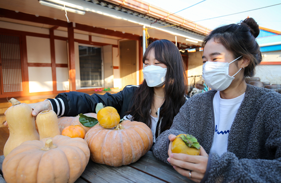 University students from Seoul smile while looking at produce in Gangjin County, South Jeolla, on Oct. 30. [JANG JUNG-PIL]