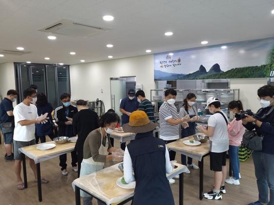 Visitors to Eco Town in Jinan County, North Jeolla, make mugwort pancakes. [JINAN COUNTY]