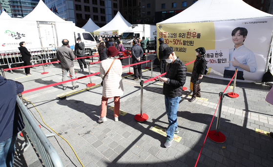 People practice social distancing Sunday at Seoul Plaza while waiting in line to purchase hanwoo (Korean beef) at special prices. The event lasts through Tuesday. [YONHAP]