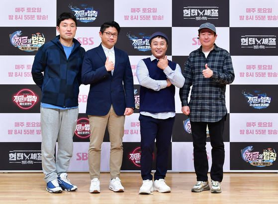 """Producers Park Yong-woo, Kim Jun-su, entertainer Kim Byung-man and producer Kim Jin-ho pose for the camera at an online press event for their variety show """"Law of the Jungle"""" on Monday. [SBS]"""