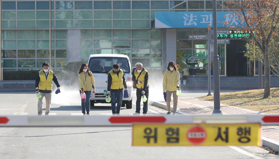 Health officials disinfect a prison in Gwangju on Monday after a worker tested positive that morning. [YONHAP]