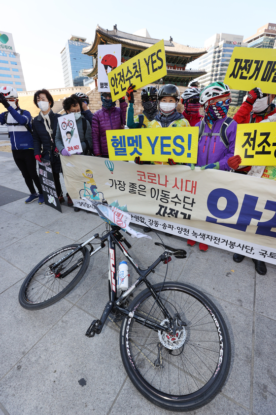 People from civic groups, including Green Bicycle For Volunteers Association and Bicycle 21, hold a press conference in Jung District, central Seoul, on Monday urging the government to come up with safety measures for electric scooters that soon will be allowed on bicycle paths. [YONHAP]