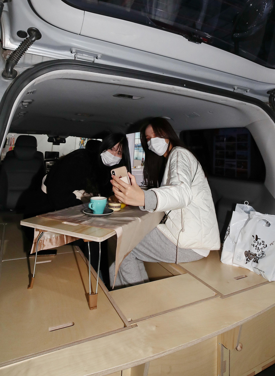 Visitors take a selfie in a camping car during 2020 Seoul International Tourism Fair held at Seoul Trade Exhibition and Convention in Gangnam District, southern Seoul, on Monday. The fair will run four days until Thursday. [YONHAP]