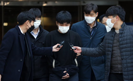 Son Jong-woo, third from left, is questioned by reporters after exiting a court hearing for a detention warrant, which was denied on Monday evening. Son is a convicted distributor of child pornography. [YONHAP]