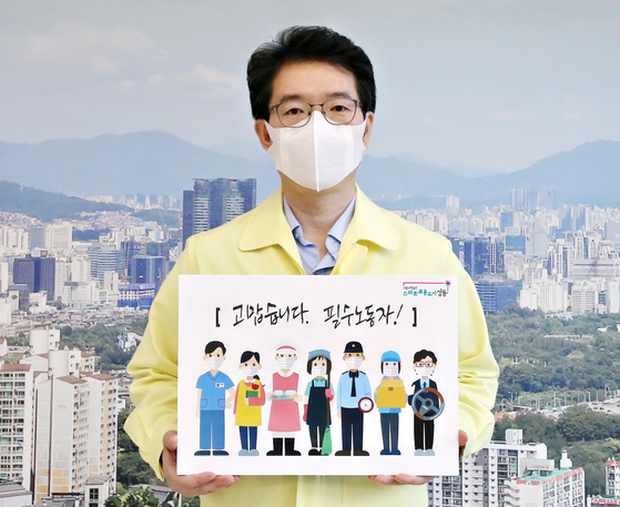 "Chong Won-o, head of the Seongdong District Government, holds up a picture for the ″Thank you, key workers"" challenge on Oct. 29, announcing that the district will provide free flu vaccines for key workers. [SEONGDONG DISTRICT OFFICE]"