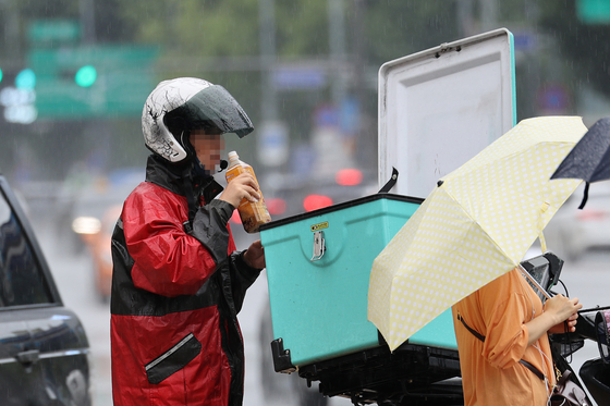 A delivery rider takes a break at Gwanghwamun, central Seoul, on Sept. 2. [YONHAP]