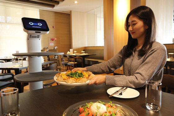 A model poses with LG Electronics' CLOi server robot at Konjiam Resort in Gwangju, Gyeonggi on Wednesday. According to LG, the resort has been expanding the number of CLOi robots in operation and currently operates five. The server robots that come with a tray or drawer attached to its body operate in the main lobby and restaurant, as well as moving between hotel rooms to serve customers. A smaller CLOi home robot helps at check out and with registering parked cars. [LG ELECTRONICS]