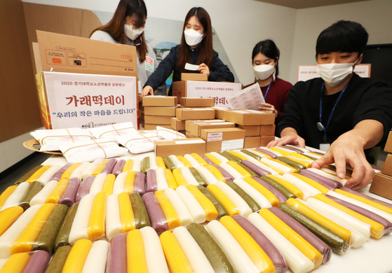 Students at Kyonggi University in Suwon, Gyeonggi, package tteok (sticky rice cake) Wednesday on the school's campus to be delivered to frontline medical workers in the city on Farmers' Day. [YONHAP]