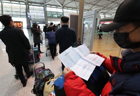 A traveler to Shenzhen, China, prepares two papers proving that they have had a negative polymerase chain reaction (PCR) coronavirus test result at a check-in counter in Incheon International Airport on Wednesday. According to the National Emergency Management Agency and Chinese Embassy, all travelers who wish to go to China from Korea must submit their negative result from a PCR test taken within 48 hours of their departures starting Wednesday. [YONHAP]