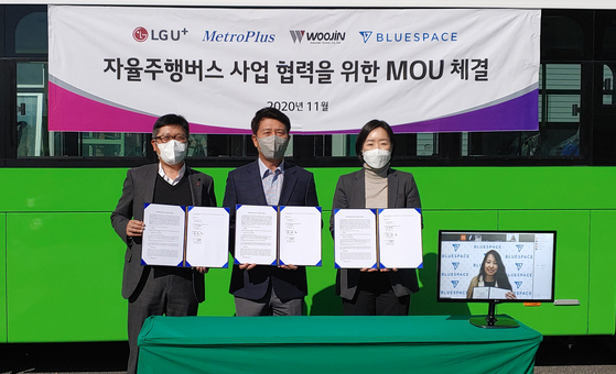 From the left, Cho Weok-seok, the senior vice president of the new business group of LG U+, Metroplus CEO Kim Tae-ho, Kim Jung-hyun, the executive managing director of Woojin Industrial Systems, and Christine Moon, president of BlueSpace.ai, during a ceremony in Woojin's factory in North Chungcheong on Tuesday. [LG U+]