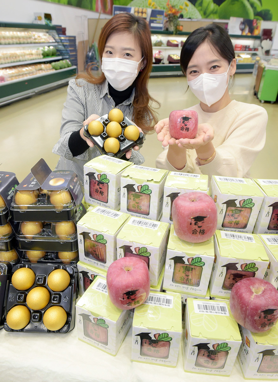 Models promote apples and eggs for the health and luck of students who are taking the upcoming College Scholastic Ability Test (CSAT) at Hanaro Mart's Yangjae branch in Seocho District, southern Seoul, on Thursday. This year's CSAT is scheduled for Dec. 3. [HANARO MART]