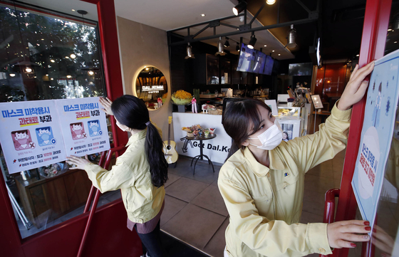 Gwangju health officials post fliers in a coffee shop Thursday informing the public they could face penalties for not wearing masks in public. [YONHAP]