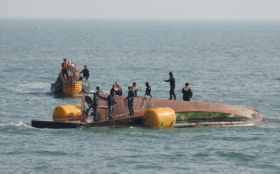 Divers conduct a search operation in waters near a northwestern border island on Sunday. A 12-ton fishing boat capsized in the sea off Soyeonpyeong Island at 6:07 p.m. Saturday, leaving three crew members, including the 63-year-old captain, missing. Two others were rescued, but one was later pronounced dead. The cause of the capsize was not immediately known. [YONHAP]