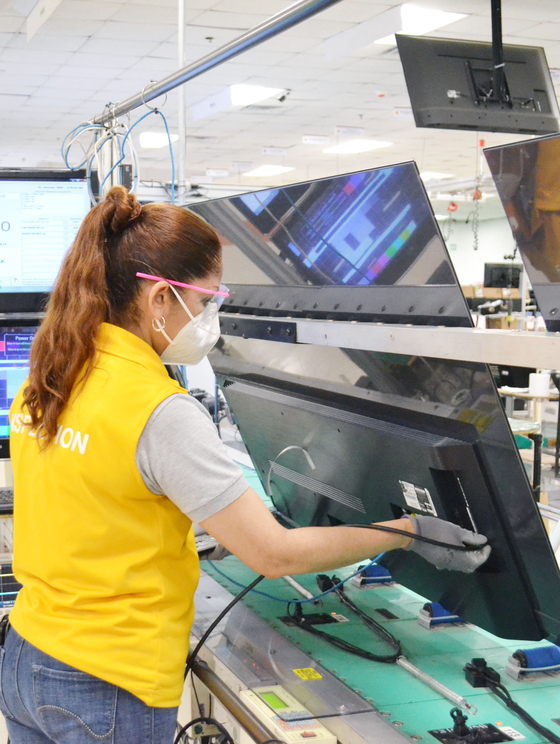 An employee is shown working on an LG Electronics TV at the company's plant in Mexico recently. According to the Korean TV manufacturer, the company has ramped up production of its high-quality TVs ahead of Black Friday in the United States. [LG ELECTRONICS]