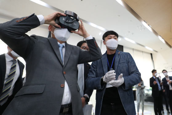 KT CEO Koo Hyun-mo wears a virtual reality (VR) headset during a VR demo at KT Square in central Seoul on Monday. The exhibition is part of a government program to connect conglomerates with start-ups. [YONHAP]