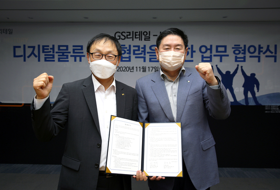 On the left, KT CEO Ku Hyeon-mo and GS Retail Vice Chairman Huh Yeon-soo during the MOU ceremony on Tuesday. [GS RETAIL]