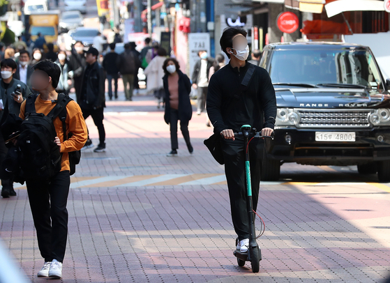 A man rides a shared electric scooter on a pedestrian road in Gangnam District, southern Seoul. [NEWS1]