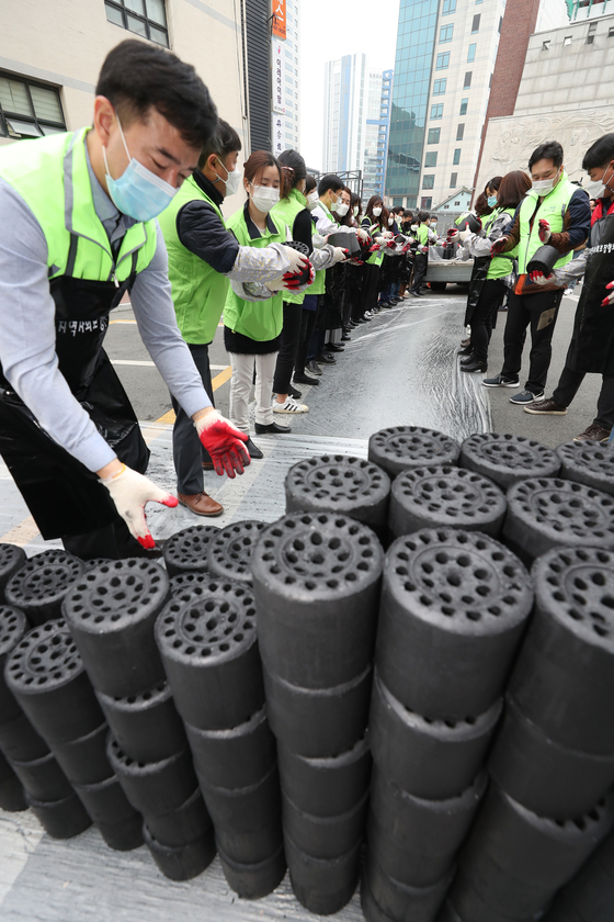 Welfare workers in Daegu on Tuesday deliver coal briquettes, a heating fuel for low-income households in a shanty town in the city.  [YONHAP]