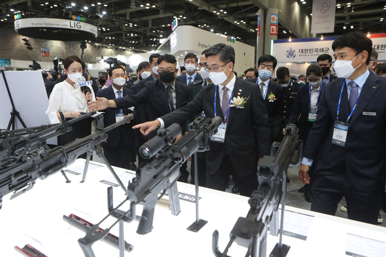 Defense Minister Suh Wook, center, looks at guns on display at the Defense & Security Expo Korea 2020, held at the Kintex Convention Center in Goyang, Gyeonggi, on Wednesday. [YONHAP]