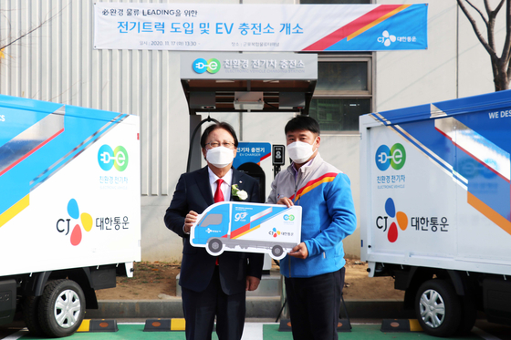 CJ Logistics CEO Park Keun-hee, left, presents an electric delivery truck to an employee in Gunpo, Gyeonggi, at an event held Tuesday to celebrate the opening of an electric vehicle (EV) charging station in the region. [CJ LOGISTICS]