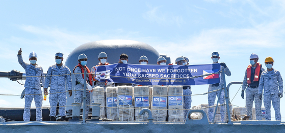 """Filipino soldiers display a banner that reads, """"Not once have we forgotten your sacred sacrifices"""" on the Conrado Yap ship in waters near Manila on Tuesday, after the Korean Navy handed over 10,000 facial masks and 2,000 units of hand sanitizer to the Philippines to express thanks to the country for fighting alongside South Korea during the 1950-53 Korean War. [YONHAP]"""