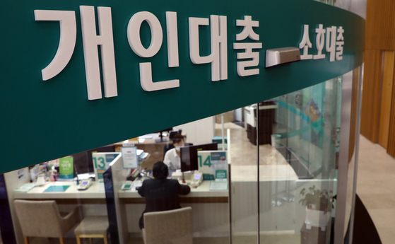 A customer consults with a bank clerk about borrowing money in central Seoul. [YONHAP]