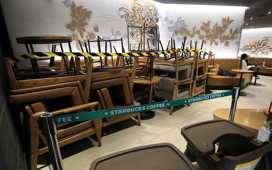 Chairs and tables are stacked up at a corner of a Starbucks coffee shop in Seoul Tuesday, as the central government warned the greater Seoul area will be subject to Level 1.5 restrictions within a week. [NEWS1]