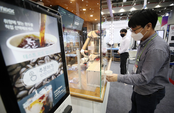 A visitor to the 2020 Korea ICT Convergence Expo tries out the services of an unmanned coffee stand and barista robot at Exco in Buk District, Daegu on Thursday. [YONHAP]