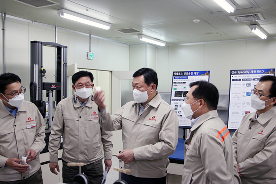 Lotte Chairman Shin Dong-bin, center, examines the production facilities at Lotte Fine Chemical's plant in Ulsan. [LOTTE FINE CHEMICAL]