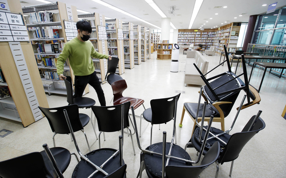 A worker at a library in Gwangju removes chairs to guarantee social distancing Wednesday as the city prepares for Level 1.5 social distancing measures. [YONHAP]