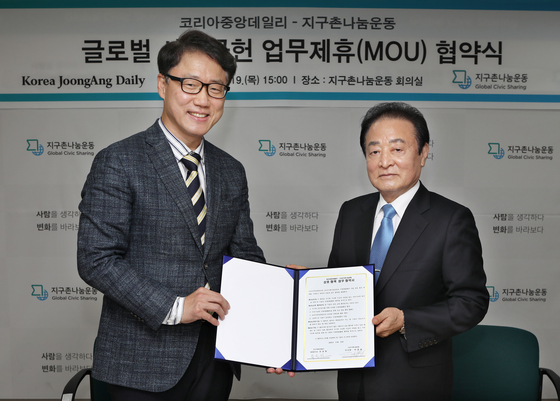 Ryu Kwon-ha, left, CEO of the Korea JoongAng Daily, and Park Myung-kwang, chairman of Global Civic Sharing, pose for a photo at the civic group's office in central Seoul on Thursday after signing a memorandum of understanding to cooperate on overseas development projects, such as poverty eradication and sustainable development in developing countries. [PARK SANG-MOON]