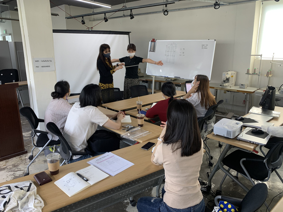 Young designers of Agoing, a fashion brand funded by the Seoul Metropolitan Government, gather at Maker Space in Yongsan District for a workshop. The area was also remodeled using city funds. [URBAN REGENERATION CENTER OF THE SEOUL METROPOLITAN GOVERNMENT]