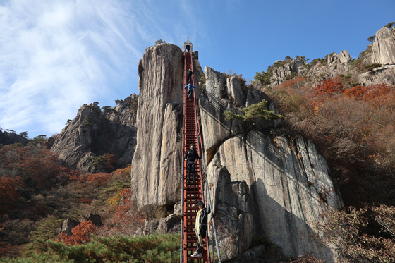 Visitors to the red staircase in Mount Daedun in Wanju County, North Jeolla, walk up, hands tightly holding onto the handles on both sides. [LEE SUN-MIN]