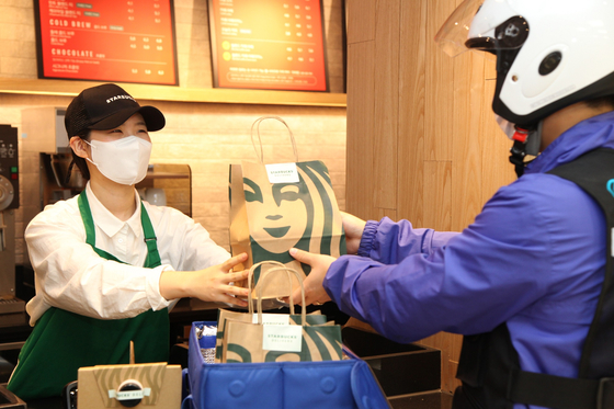 A Starbucks employee hands over a delivery order during a test ahead of the launch of the pilot program next week. [STARBUCKS KOREA]