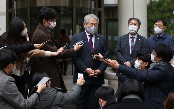 Kim Yong-ik, president of the National Health Insurance Service, center, speaks to reporters outside the Seoul Central District Court on Friday. [YONHAP]
