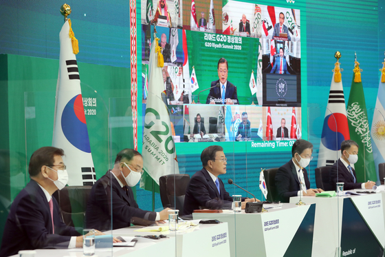 Korean President Moon Jae-in, center, flanked by aides, speaks during a virtual summit of the Group of 20 (G-20) leaders of major economies at the Blue House on Saturday. [JOINT PRESS CORPS]