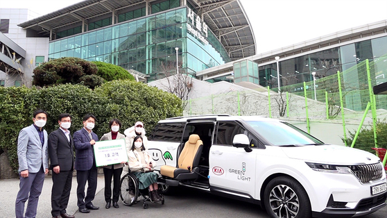 Employees at Korea Railroad pose in front of the first modified vehicle for the disabled after signing a memorandum of understanding (MOU) with Kia Motors on Monday. From 2021, the partner companies will sponsor for two years round-trip KTX tickets and the customized vehicle as well as transportation expenses for 500 families with family members with disabilities. [YONHAP]