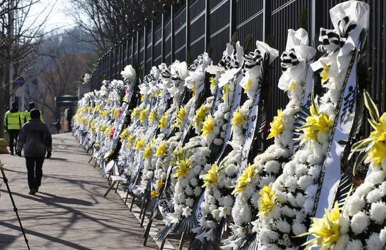 People walk past flower arrangements set up to protest Justice Minister Choo Mi-ae at the Gwacheon Government Complex in Gyeonggi on Monday. [NEWS1]