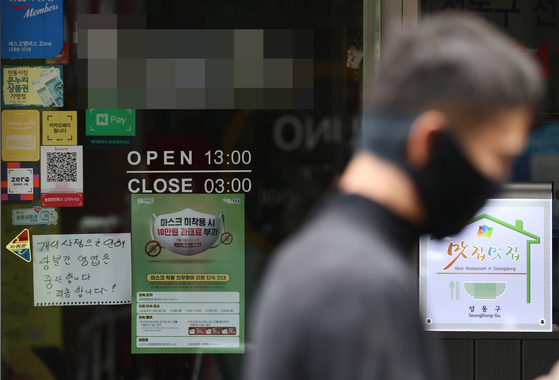 A man wearing a face mask walks past a restaurant with a temporary closure notice in Seoul. [YONHAP]