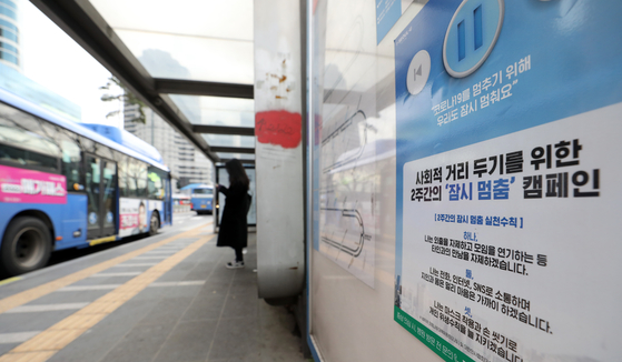 Starting Tuesday, buses are running at 80 percent of their normal frequencies after 10 p.m., as part of the Seoul city government's social distancing measures. Subways in the city will also reduce frequencies by 20 percent after 10 p.m., starting Friday. A sign is placed at a bus stop in central Seoul notifying the public of the reduction of buses. Level 2 social distancing recommendation is in place in the greater Seoul area starting Tuesday. [NEWS1]