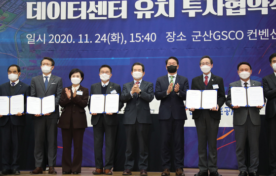 Prime Minister Chung Sye-kyun, fifth from left, and SK Group Chairman Chey Tae-won, sixth from left, pose at a ceremony to mark SK's investment in the Saemangeum Development Project at Gunsan Saemangeum Convention Center in Gunsan, North Jeolla on Tuesday. SK Group will invest 2.1 trillion won ($1.89 billion) into the creation of data centers and entrepreneurship infrastructure in the Saemangeum Industrial Complex. [YONHAP]