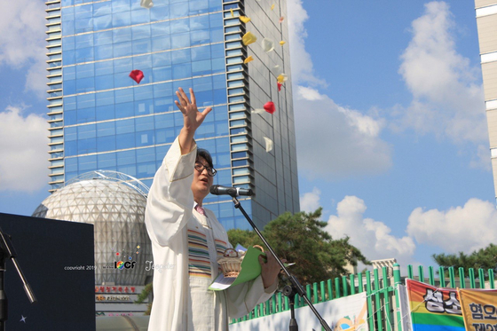 Pastor Lee Dong-hwan throws petals into the air while giving a blessing on Aug. 31, 2019, at the second Incheon Queer Culture Festival. [YONHAP]