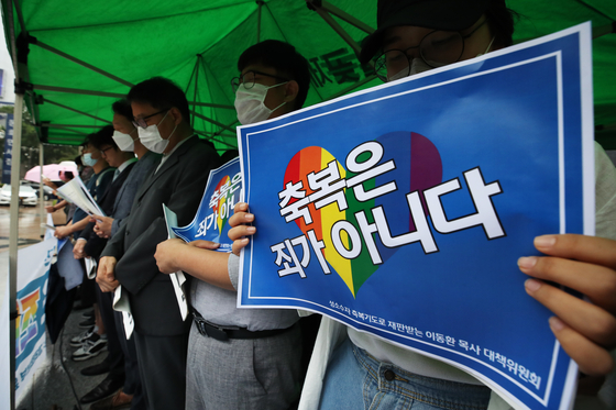 Protestors hold a card reading ″A blessing is not a sin″ on June 24 in front of the Korean Methodist Church headquarters in Gwanghwamun, central Seoul, demanding the church revoke its decision to suspend Lee. [YONHAP]